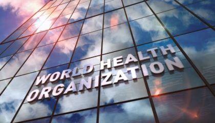 World Health Organization glass building. Mirrored sky and city on modern facade. WHO, emergency, healthcare, epidemic, virus, help, prevention and medical concept in 3D rendering illustration.